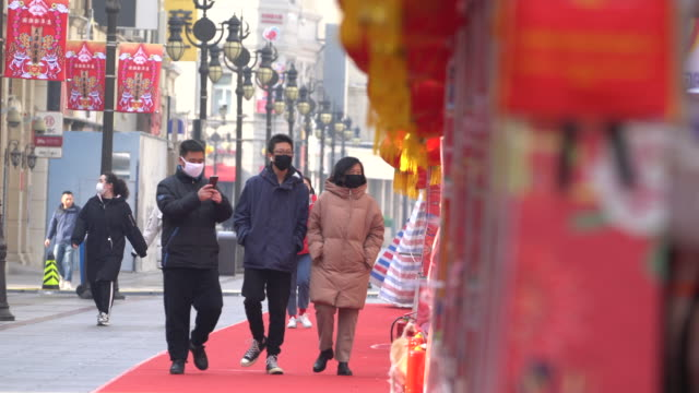 people wearing masks walking past empty boothes formerly ready for temple fair and now called off on the famous business street of binjiang dao at... - coronavirus stock videos & royalty-free footage