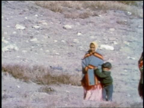 vídeos y material grabado en eventos de stock de 1957 people wearing native dress + brightly colored blankets walking outdoors / may be south america - 1957