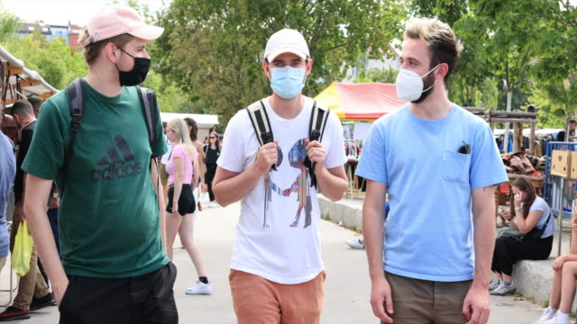 stockvideo's en b-roll-footage met people wearing protective face masks enjoy the sunny and warm summer weather at a flea market in the mauerpark in the district prenzlauer berg during... - tourism