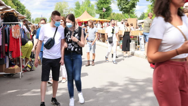 people wearing protective face masks enjoy the sunny and warm summer weather at a flea market in the mauerpark in the district prenzlauer berg during... - tourism stock videos & royalty-free footage