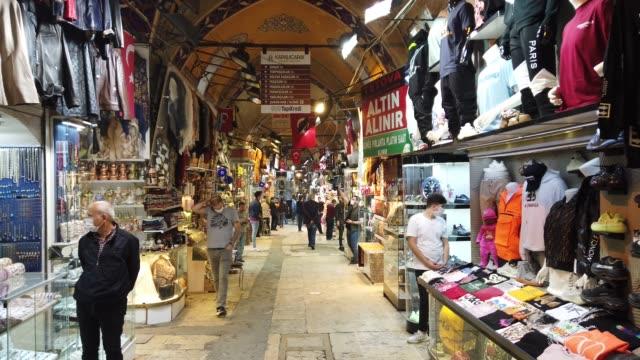 stockvideo's en b-roll-footage met people wearing protective face masks walk in the grand bazaar after it reopened after being shut down for weeks due to the spread of the coronavirus... - grote bazaar van istanboel istanboel