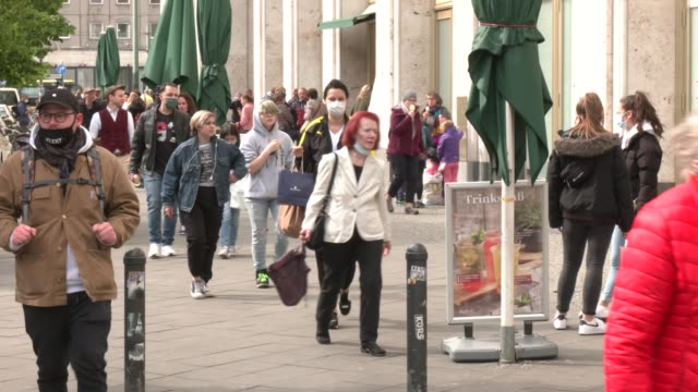 vidéos et rushes de people wearing protective face masks walk next to a shopping mall galeria kaufhof department store at alexanderplatz during the coronavirus crisis on... - allemagne