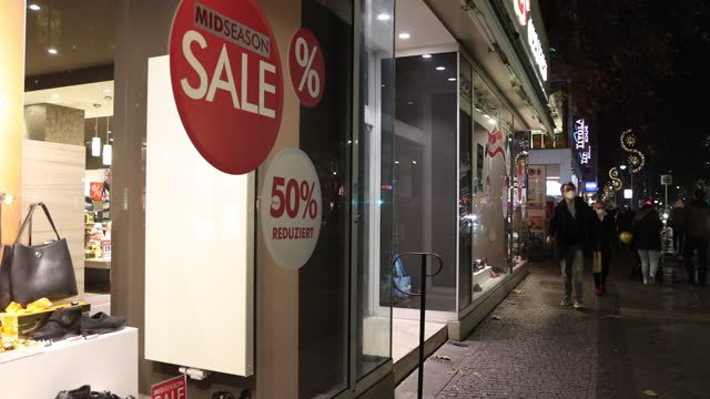 people wearing protective face masks walk past a shoe store advertising sales on schlossstrasse, a popular shopping street in district steglitz on... - selling stock videos & royalty-free footage