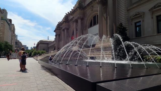 people wearing protective masks admire the water fountain outside the metropolitan museum of art, aka the met, as the city continues phase 4 of... - metropolitan museum of art new york city stock videos & royalty-free footage