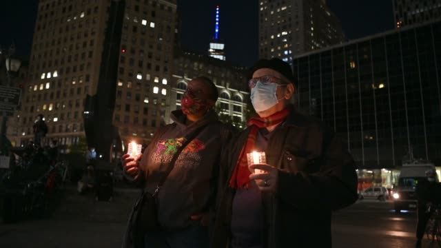 people wearing protective masks and holding candles pay their respects to late u.s. supreme court justice ruth bader ginsburg outside the new york... - new age stock-videos und b-roll-filmmaterial