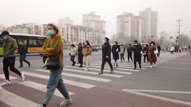 people wearing protective masks cross a street during a sandstorm on march 15, 2021 in beijing, china. the chinese capital and the northern parts of... - beijing stock videos & royalty-free footage