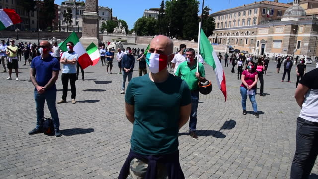 people wearing protective masks gather holding the italian flag as the far-right political movement casapound listens to speakers and protests... - italienische flagge stock-videos und b-roll-filmmaterial