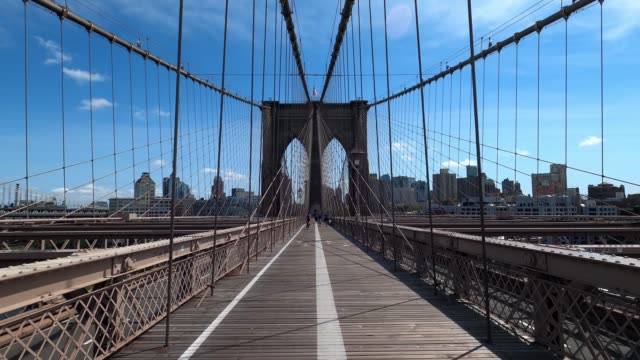 people wearing protective masks walk across a nearly empty brooklyn bridge on labor day as the city continues phase 4 of reopening following... - brooklyn bridge stock videos & royalty-free footage