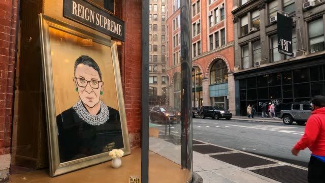 people wearing protective masks walk past a painting of the late u.s. supreme court justice ruth bader ginsburg displayed in a shop window in the... - supreme court justice stock videos & royalty-free footage