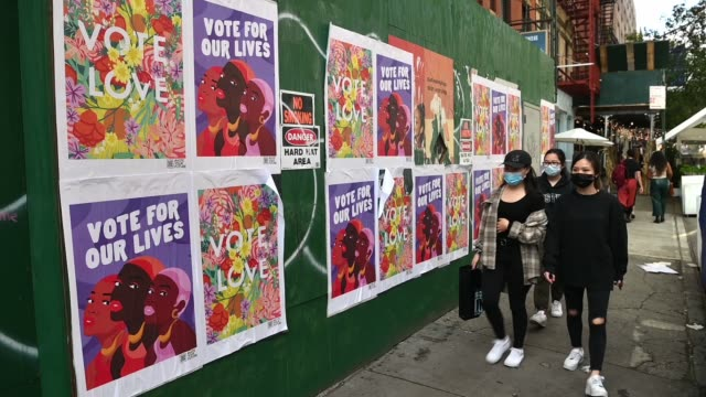 """stockvideo's en b-roll-footage met people wearing protective masks walk past political signage that reads """"vote for our lives"""" and """"vote love"""" in soho on october 20, 2020 in new york... - redactioneel"""
