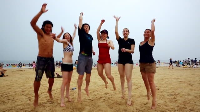 MS SLO MO People wearing swimsuits and jumping on daecheon beach / Boryeong, Chungcheongnam-do, South Korea