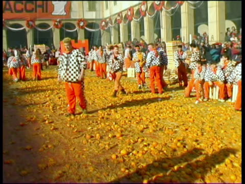 ms ws pov people wearing traditional costumes walking on smashed oranges on city square / ivrea, torino, italy / audio - western script stock videos & royalty-free footage