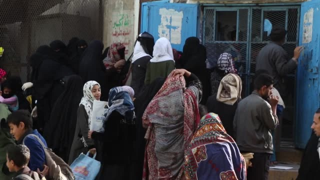 people who were affected by the the war now, gather to receive free breads as aids from a charity center in sana'a - yemen stock videos & royalty-free footage