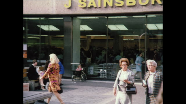 stockvideo's en b-roll-footage met montage people window shop and eat lunch at a mall / uk - 1970