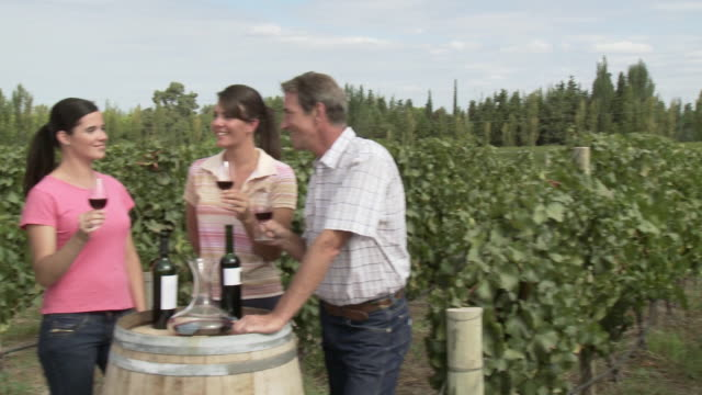 People wine tasting in a vineyard, raising glasses to the camera