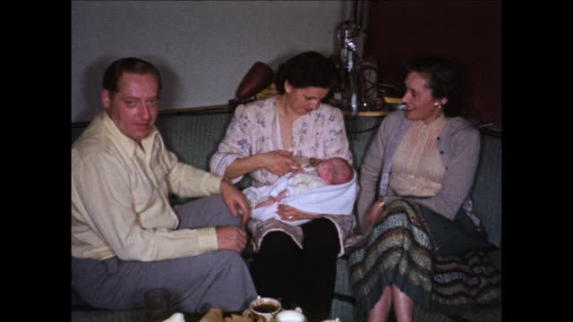 stockvideo's en b-roll-footage met 1955 montage people with baby girl (12 months) sitting on couch, feeding baby / toronto, canada - zuigfles
