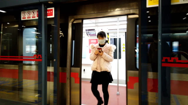 people with face mask protection in metro station,xi'an,china. - 地下点の映像素材/bロール