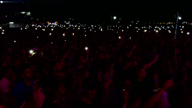vídeos de stock e filmes b-roll de people with flashlights at a rock concert - evento de entretenimento