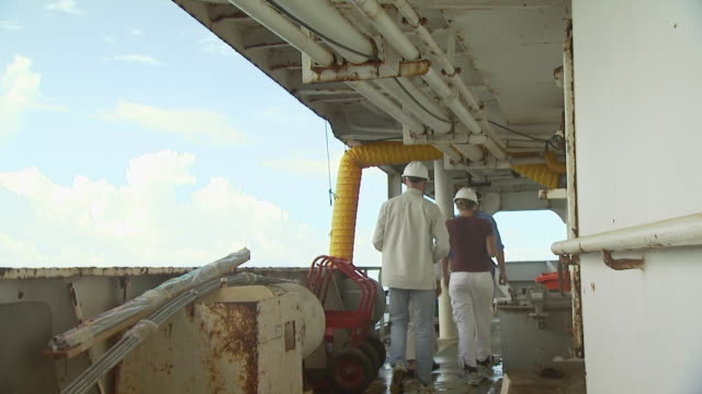 people with hard hats walk on rusty ships deck, australia - imperfection stock videos & royalty-free footage