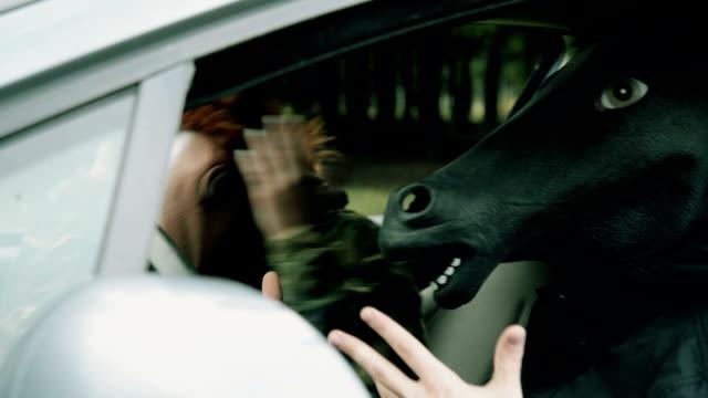 Menschen mit Pferd Kopfmaske im Auto