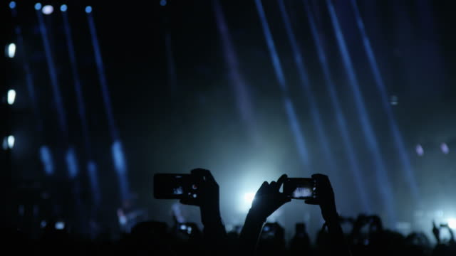 vídeos de stock e filmes b-roll de people with mobile phones at a music concert - rocking