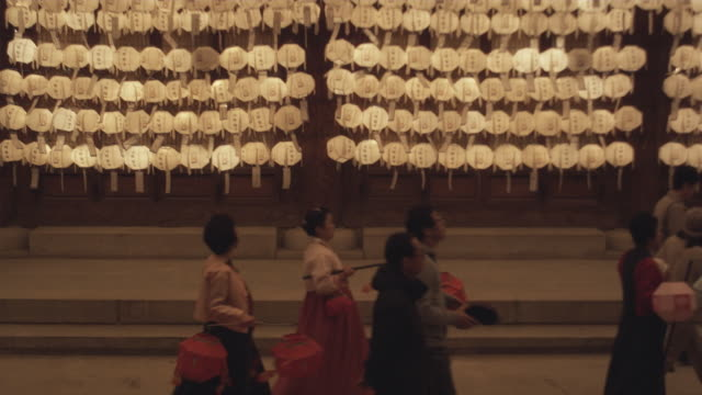 ms ha people with paper lanterns walking in front of jogyesa temple, white paper lanterns hanging in background, buddha's birthday, seoul, south korea - buddha's birthday stock videos and b-roll footage