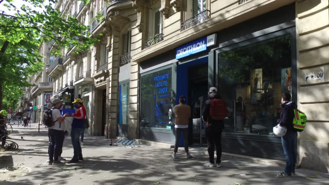 vidéos et rushes de people with protective masks stand in line in front of an open store, decathlon on boulevard saint-germain, 75005 paris, on may 11, 2020 in paris,... - boutique