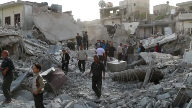 people with rescue team inspect the collapsed buildings and try to rescue people after assad regime forces' airstrike over residential areas in... - guerra video stock e b–roll
