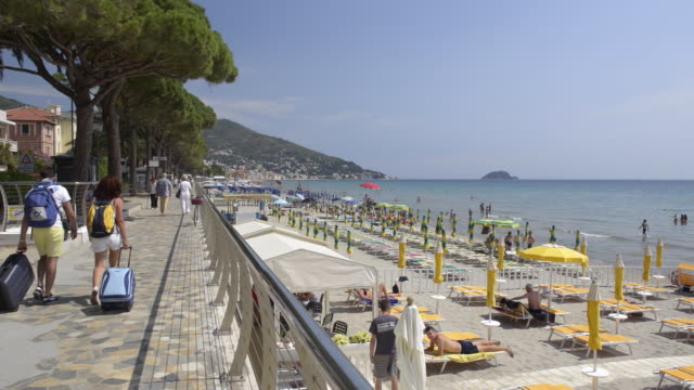 people with suitcase walk on promenade at alassio beach - boundary video stock e b–roll