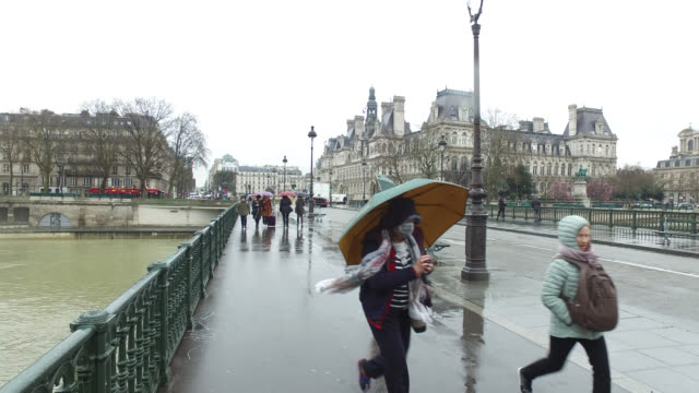 people with umbrellas at center of paris - frankreich stock-videos und b-roll-filmmaterial