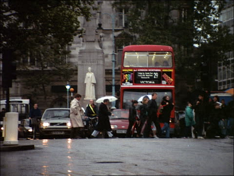 pan people with umbrellas crossing london city street in front of stopped traffic in rain / london - 2001 stock videos and b-roll footage