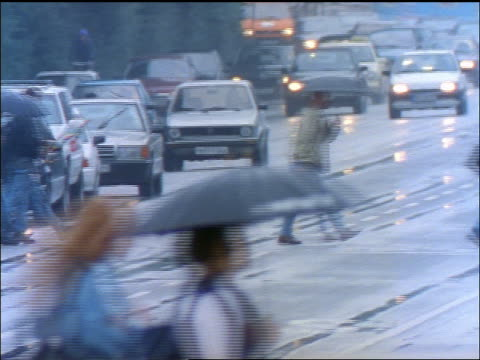 people with umbrellas crossing wide busy street with traffic in rain / hamburg, germany - 1998 stock-videos und b-roll-filmmaterial