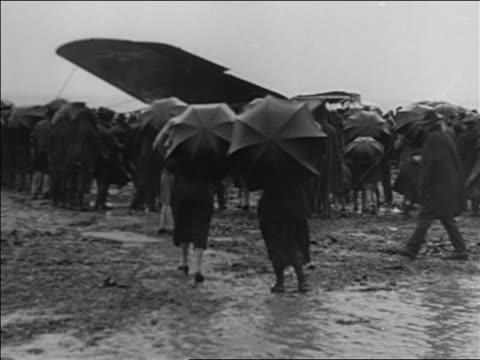 view people with umbrellas crowd around admiral byrd's airplane wreckage / france - 1927年点の映像素材/bロール