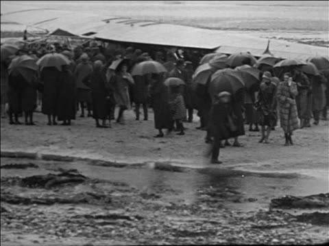 people with umbrellas crowd around admiral byrd's airplane wreckage / france - anno 1925 video stock e b–roll