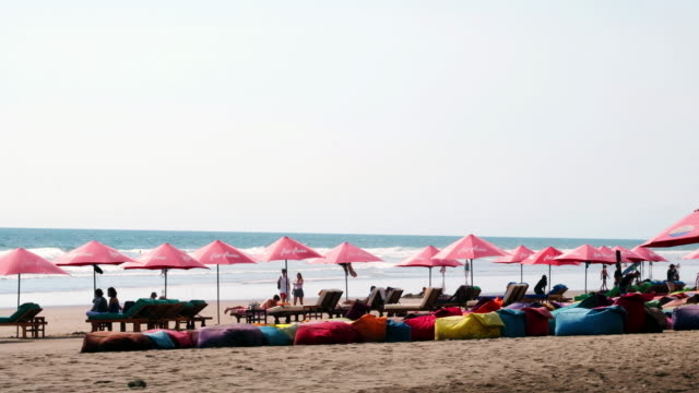people with umbrellas on the beach in bali, indonesia. - indonesia stock videos & royalty-free footage