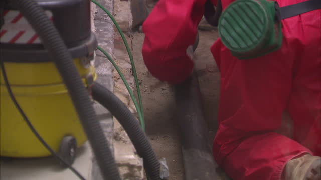 people wokring in red boiler suits and face masks in a dust filled room repairing a pipe - shows workers clearing asbestos from the ducts in the... - アスベスト点の映像素材/bロール