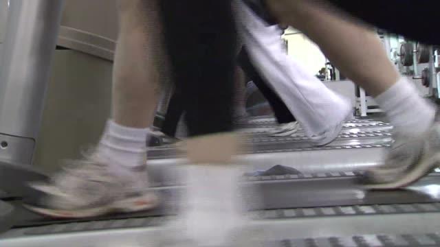 vídeos y material grabado en eventos de stock de people work out on treadmills, elliptical machines and get advice from personal trainer. - entrenamiento sin material