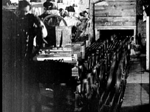 stockvideo's en b-roll-footage met b/w, montage, people working at car assembly line in factory, 1900's, detroit, michigan, usa - film industry
