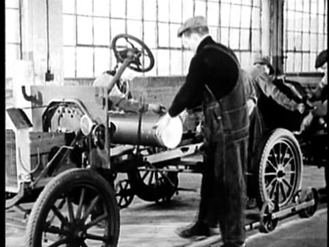 b/w, montage, people working at ford model t assembly line in factory, 1900's, detroit, michigan, usa - 自動車産業点の映像素材/bロール