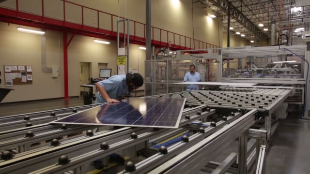 people working at suntech solar panel factory / workers inspecting processing and packaging solar panels / large crates of solar panels with suntech... - sustainable energy stock videos & royalty-free footage