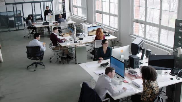 クリエイティブなスタートアップオフィスで働く人々 - フリーアドレス点の映像素材/bロール