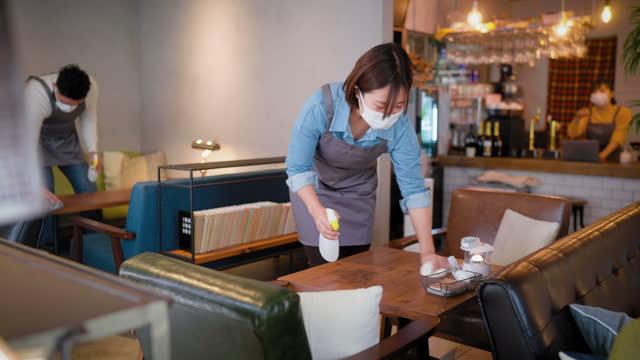 カフェを再開する前に、保護フェイスマスクを着用し、テーブルを消毒してカフェで働く人々 - 衛生管理点の映像素材/bロール