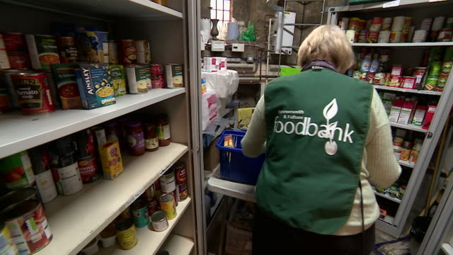 people working in food bank, putting food into baskets, london - basket stock videos & royalty-free footage