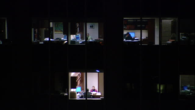 MS, People working in in office building at night, view through windows, New York City, New York, USA