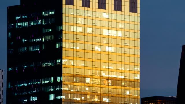 TL D2N TD människor arbetar i kontorsbyggnad urbana staden, scen Visa byggnaden spegel reflekterar solljus förändring till neon ljus inuti.