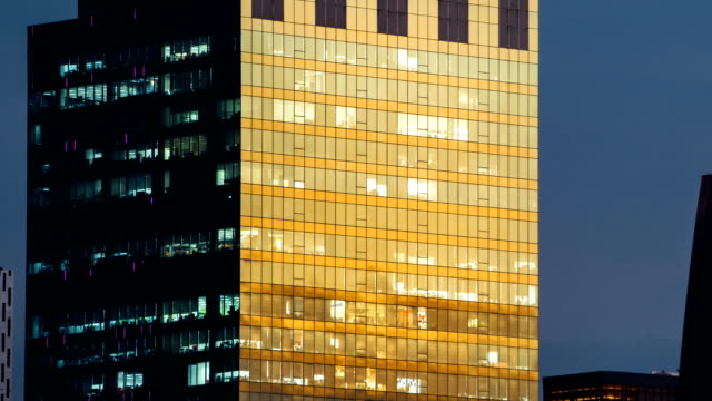 TL D2N TD People working in office building urban city, scene show building mirror reflect sunlight change to neon light inside.