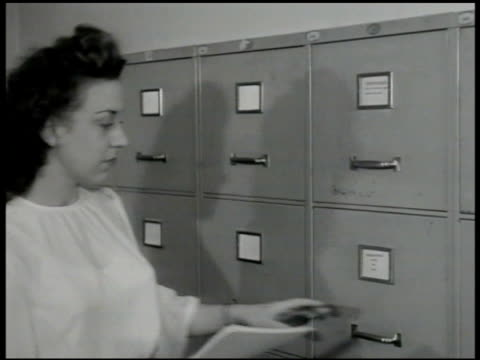 people working in office paperwork on telephone filing female worker opening full file drawer cu report cover 'institutions for dependent children'... - 1946 stock videos and b-roll footage