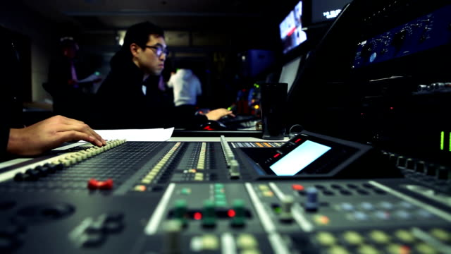 people working in television broadcasting control room - sala di controllo video stock e b–roll