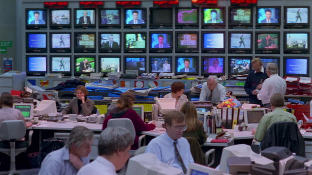 t/l, ms, people working in television news room, tv screens in background - journalist video stock e b–roll