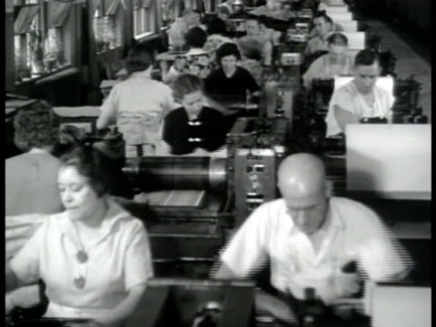 vídeos de stock, filmes e b-roll de invasion dollars people working on table top printing machines cu chain pulling press forward hand pulling sheet of bills off plate ms stacks of... - 1943